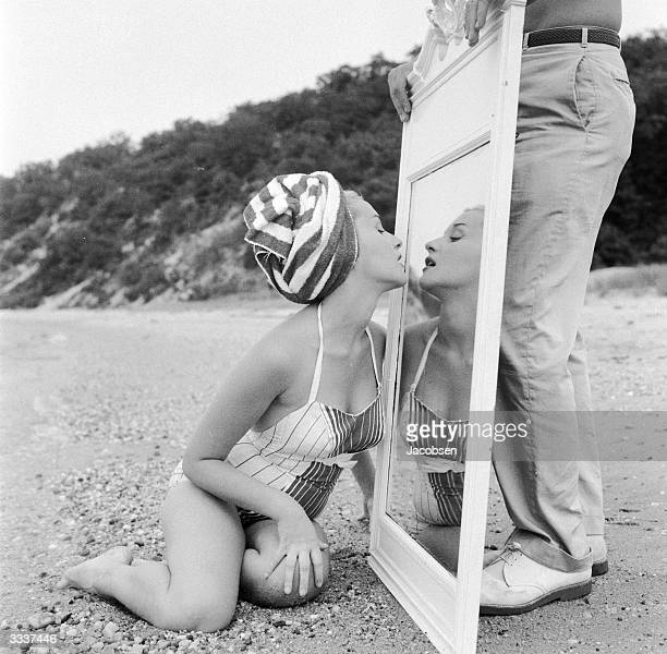 A girl on a beach checking her lipstick in a mirror