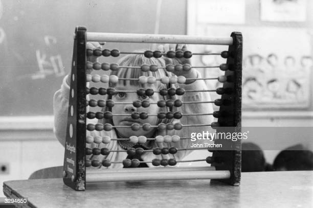 A Haole girl learns to count on an abacus the Chinese method of addition