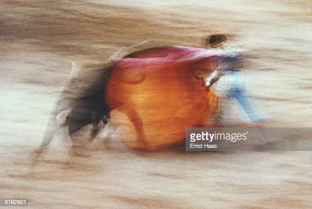 A matador twirls his red cape to confuse the bull during a Spanish bullfight