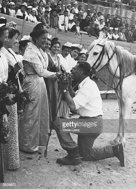 A matador who has just snared a cockade from a bull kisses the hand of an admiring fan as she presents him with flowers