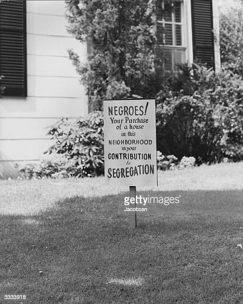 A sign in the grass outside a house belonging to a black family at Lakeview Long Island where members of the black community are trying to limit the...