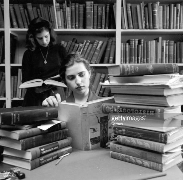 A student at Sarah Lawrence College in New York with a pile of books
