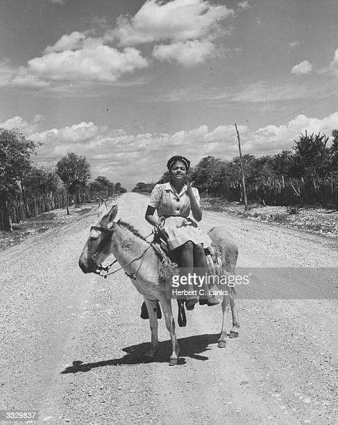 A woman riding her donkey sidesaddle in the Dominican Republic