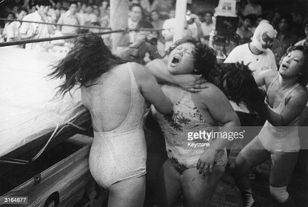 A wrestler hooks her arm around her opponent's neck as a group of women wearing swimsuits fight outside the ring