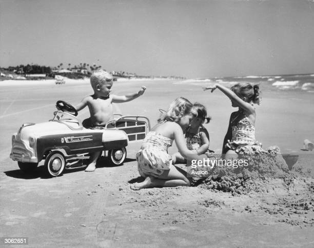 A young boy trying to impress three girls in his pedal car on Daytona Beach Florida