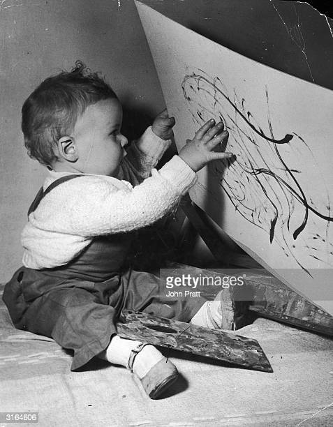 A young child closely inspects a painting