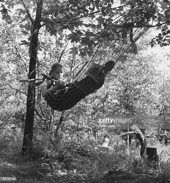 A young Finnish girl Leena reading a book in a hammock amongst the trees in the afternoon