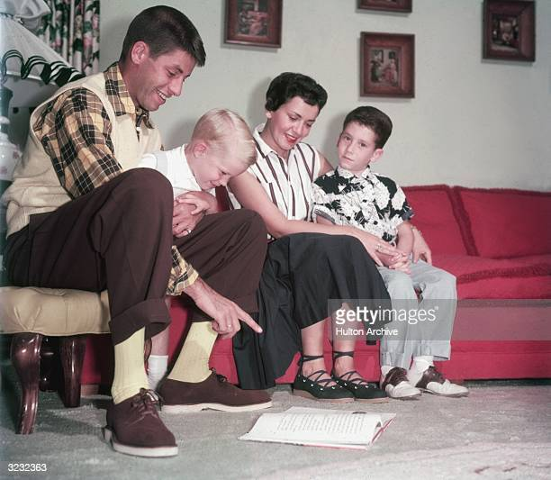American actor and comedian Jerry Lewis sitting on a couch with wife Patti Palmer and their two sons Gary and Ronald