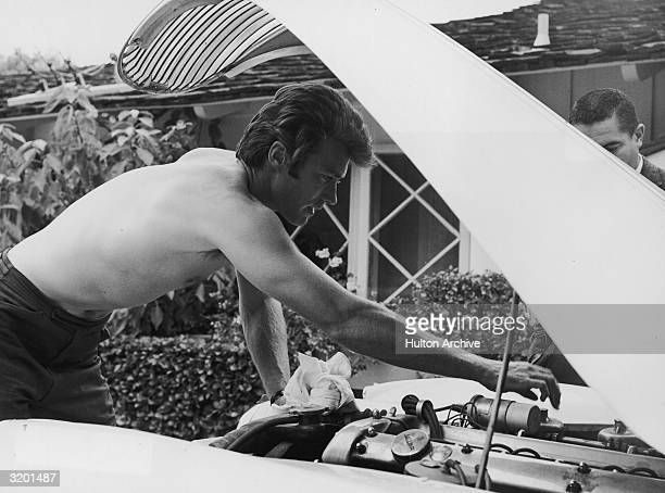 American actor Clint Eastwood bare chested leans forward under the hood of a Jaguar car while repairing its engine outdoors in front of a house