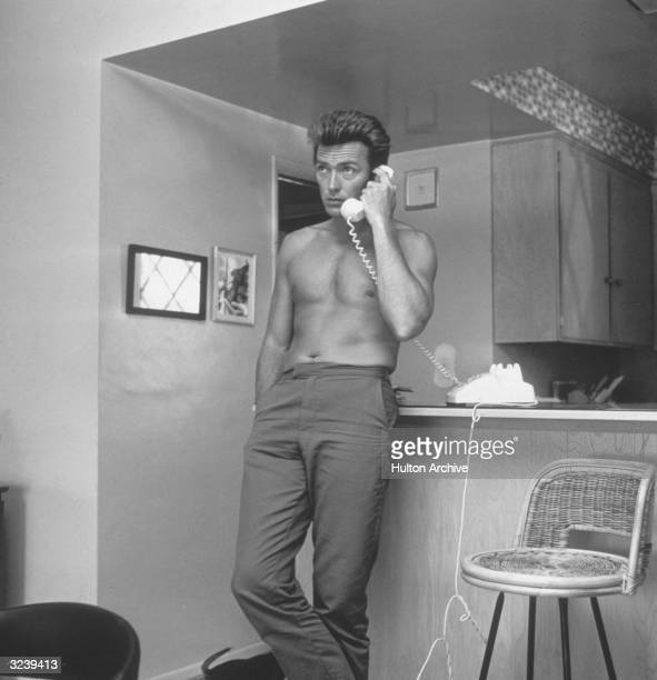 American actor Clint Eastwood leans against a kitchen counter barechested while speaking on the telephone from his home