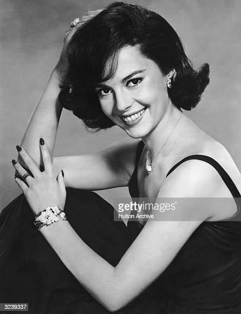 American actor Natalie Wood, wearing a black evening dress, smiles while posing in a promotional portrait for director Michael Anderson's film, 'All...