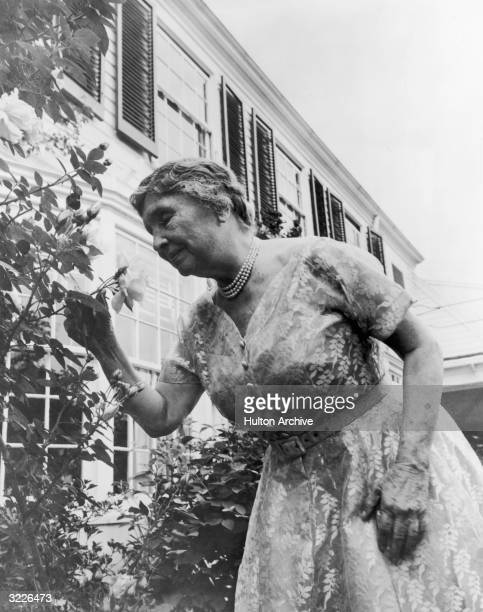 American author and lecturer Helen Keller , aged 80, sniffs a rose at the side of a house. Deaf and blind from an early age, she learnt to...