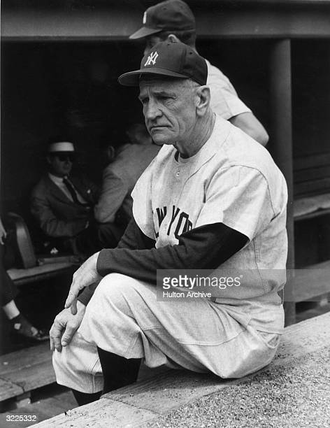 American baseball manager Casey Stengel sits on the edge of the New York Yankees' dugout wearing his uniform From 1949 to 1960 he led the club to ten...