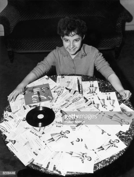 American pop and country singer Brenda Lee sits on the floor behind a coffee table covered with copies of her album 'Brenda Lee' and press clippings...