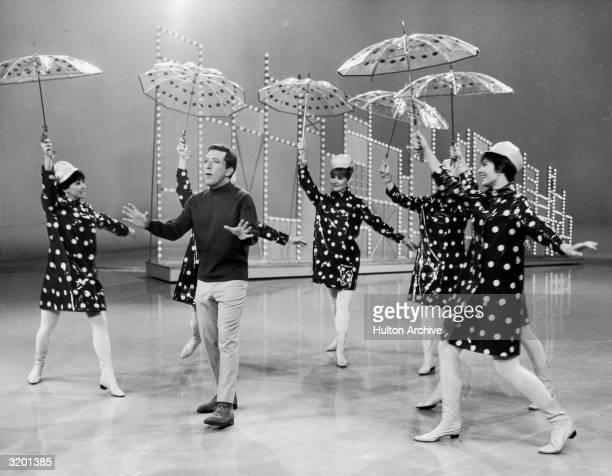 American pop singer Andy Williams performs as dancers circle him wearing polkadot raincoats and holding polkadot umbrellas in his television variety...