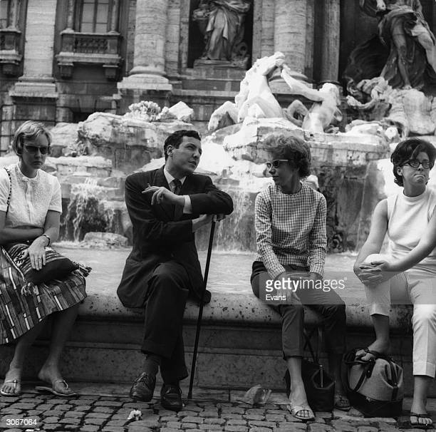American tourists sitting on the edge of the Fountain of Trevi in Rome