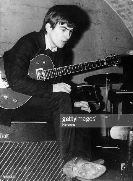 Beatle George Harrison with his guitar tucked under his arm, taking a break from playing at the Cavern, Liverpool.