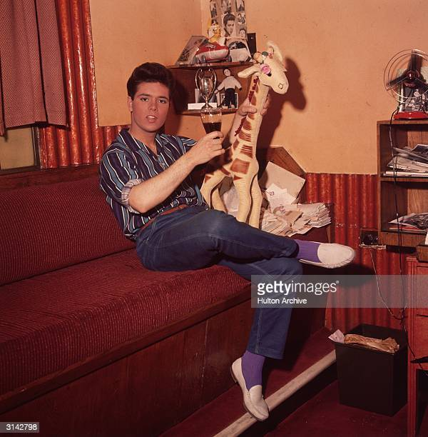 Cliff Richard shares a glass of wine with a toy giraffe