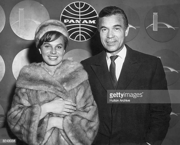 Dominican diplomat Porfirio Rubirosa poses with his wife for the cameras with a PanAm Airlines Iogo behind them New York International Airport New...