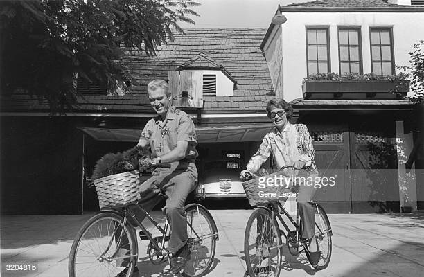 EXCLUSIVE American actor James Stewart and his wife Gloria Hatrick McLean ride bicycles in the driveway of their home in California Their pet poodle...