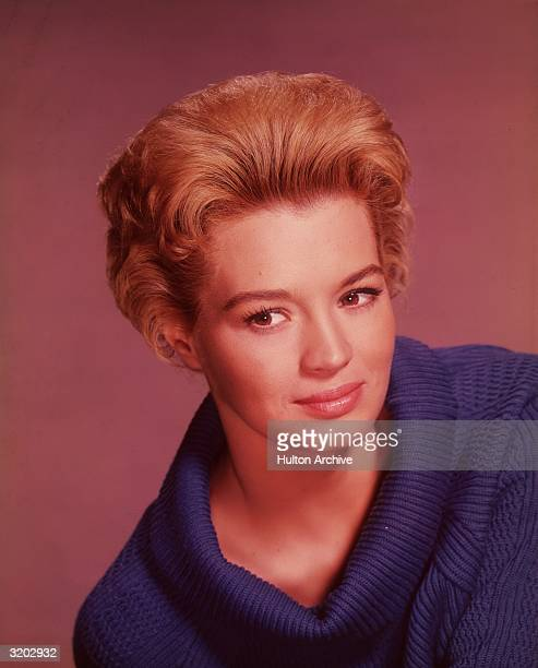 Headshot studio portrait of American actor Angie Dickinson smiling in a blue cowlnecked sweater in front of a pink backdrop