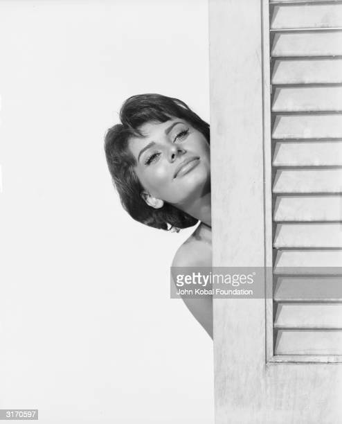 Italian actress and sex symbol Sophia Loren looks out enticingly from behind a door