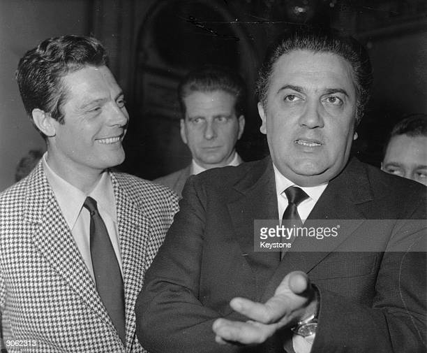 Italian filmmaker Federico Fellini with the actor Marcello Mastroianni during a press conference in Paris promoting the film 'La Dolce Vita'