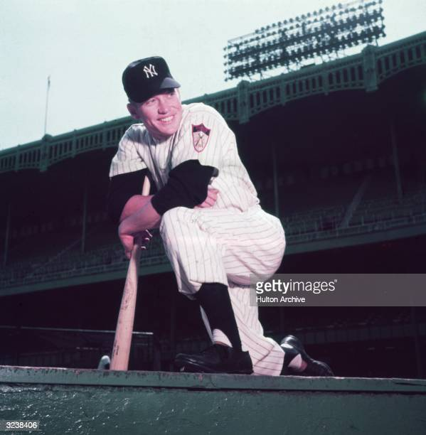 Lowangle portrait of American baseball player and New York Yankees outfielder Mickey Mantle in uniform smiling and kneeling on one leg on the ground...