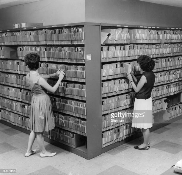 Office workers filing the many insertion orders sent by companies all over the United States requesting advertising space in the Yellow Pages...
