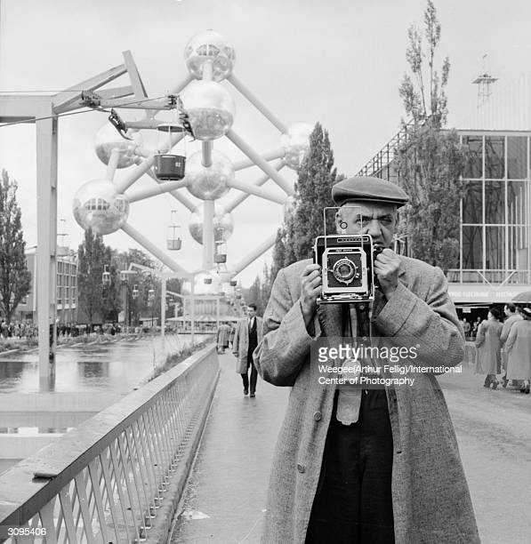 Polishborn American photographer Arthur 'Weegee' Fellig in Brussels in front of the famous Atomium built for the Brussels World Fair in 1958 Photo by...