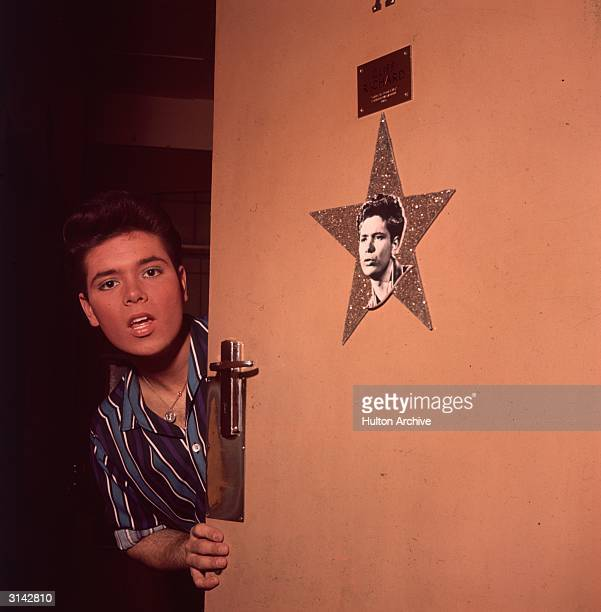 Pop star Cliff Richard peers round his dressing room door which is decorated with a star
