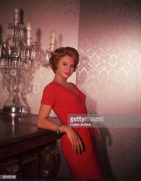 Portrait of Indianborn actor Juliet Prowse wearing a red dress and leaning against a table