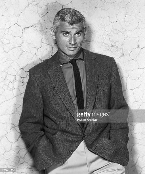Promotional portrait of American actor Jeff Chandler leaning against a stone wall with his hands in his pockets
