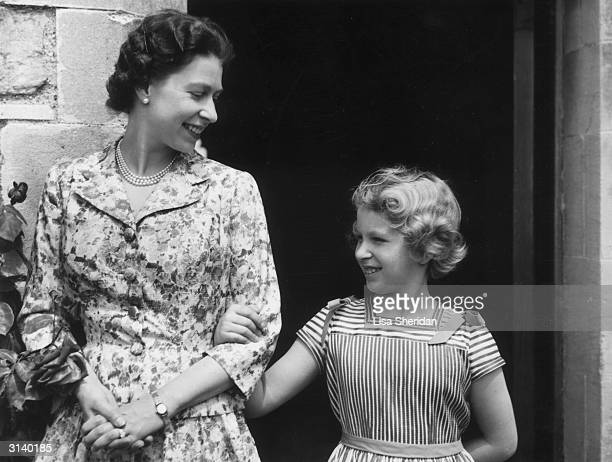Queen Elizabeth II with her only daughter and second child Princess Anne arminarm in the gardens of Windsor Castle
