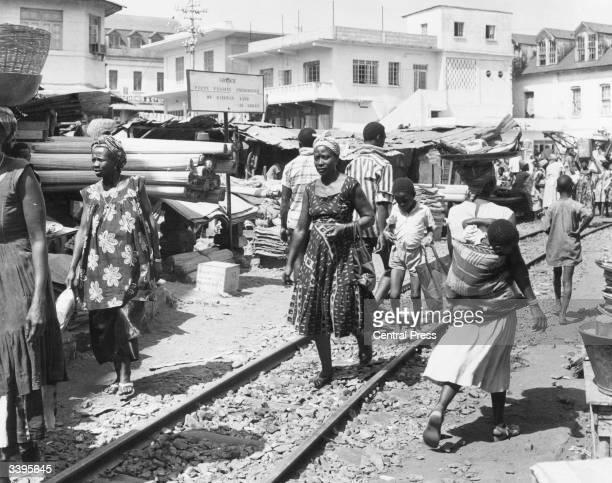 Shoppers walking across a railway track running through Central Market Avenue of Freetown Sierra Leone