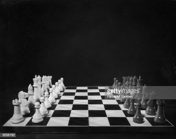 Stilllife of a chessboard with its dark and light game pieces assembled for play in front of a black backdrop