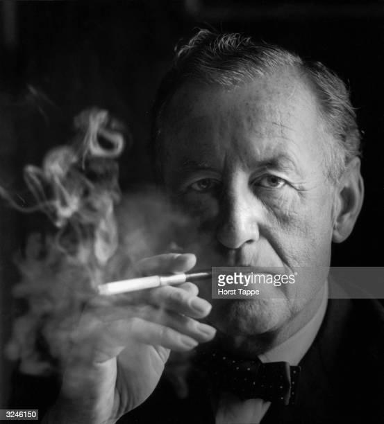 Studio headshot portrait of British author Ian Fleming the creator of James Bond smoking a cigarette in a holder