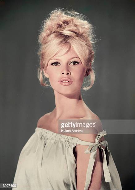 Studio portrait of actor and model Brigitte Bardot wearing a light blue off-the-shoulder dress.