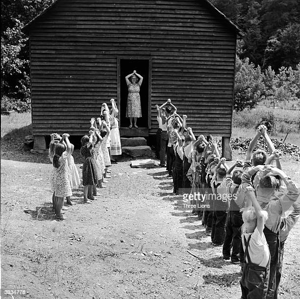 The entire class of a one room grade school in rural Kentucky, hold their hands over their heads to get any kinks out of their young bones. The...