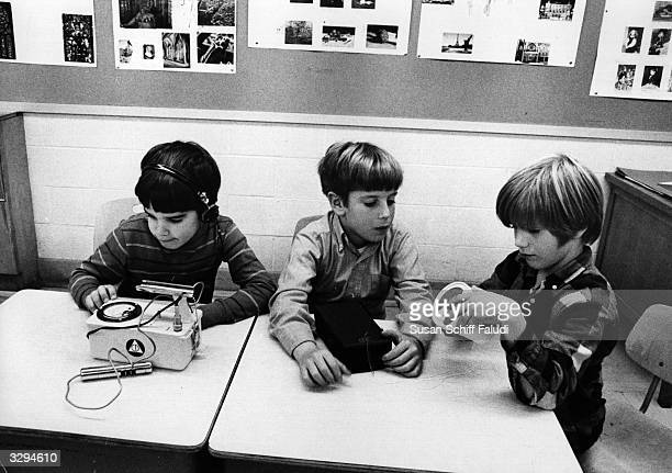 The young child on the left is examining a real geiger counter, whilst his colleagues compare their models with the real thing.