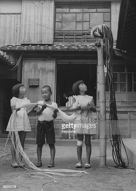 Three children from the island of Shikoku Japan with two long tailed roosters known as 'NagaoDori' a rare species bred by crossing pheasants and...