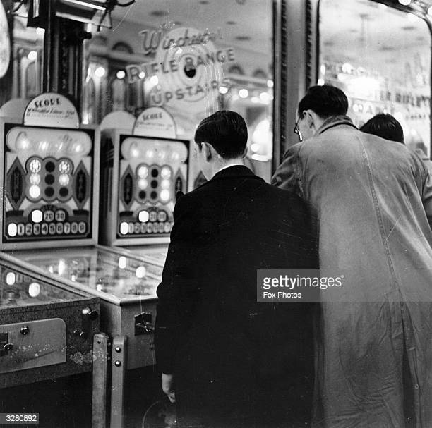 Two people looking at pinball machines in an amusement arcade
