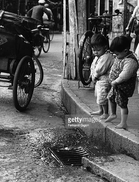 Two young boys urinating in a street in China
