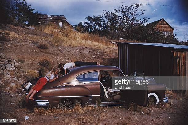 Two young girls play on car abandoned by some old huts in stoney countryside