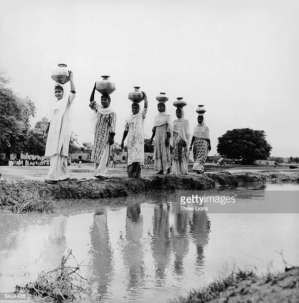 Women carrying copper water jars on their heads walk beside an irrigation canal in Maryabad a Christian village some 60 miles from Lahore