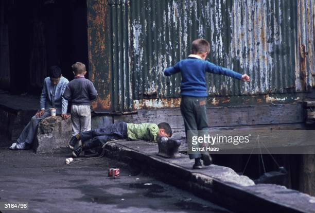 Young boys playing on a low parapet in New York County