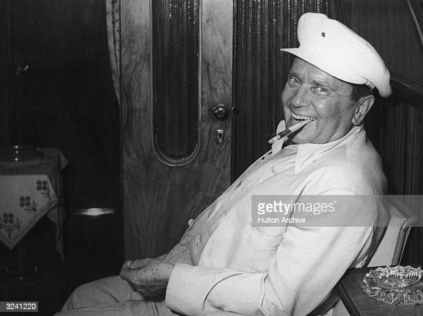 Yugoslav President Josip Broz Tito sitting in a cabin on a chair against the wall smiling and smoking a cigarette with a long filter