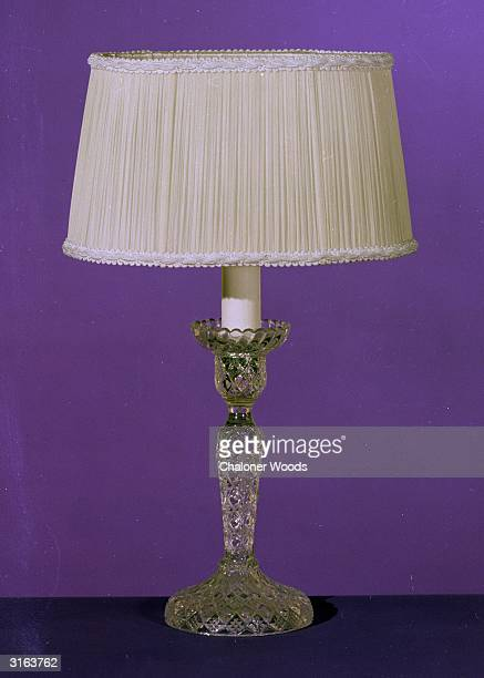 A table lampshade mounted on a cut glass stand for subdued lighting