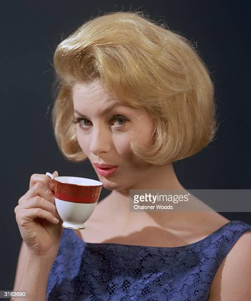 A wellgroomed young woman quenching her thirst with a cup of strong coffee