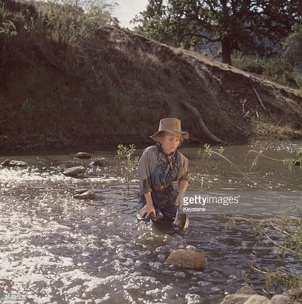 American actress and singer Debbie Reynolds panning for gold in one of her films